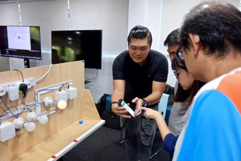 A workshop trainer showing participants how to use a Smart Home device