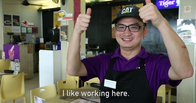 A restaurant employee smiling and giving a thumbs up