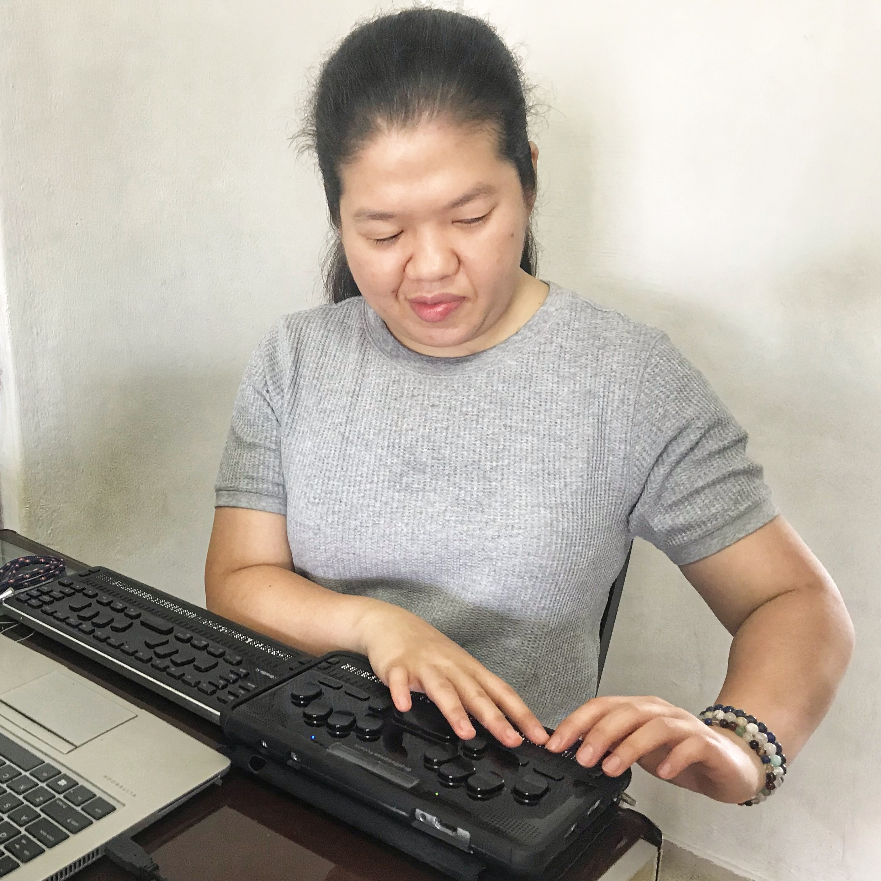 A picture of Siew Ling reading with the use of BrailleSense Polaris and BrailleSense QBraille