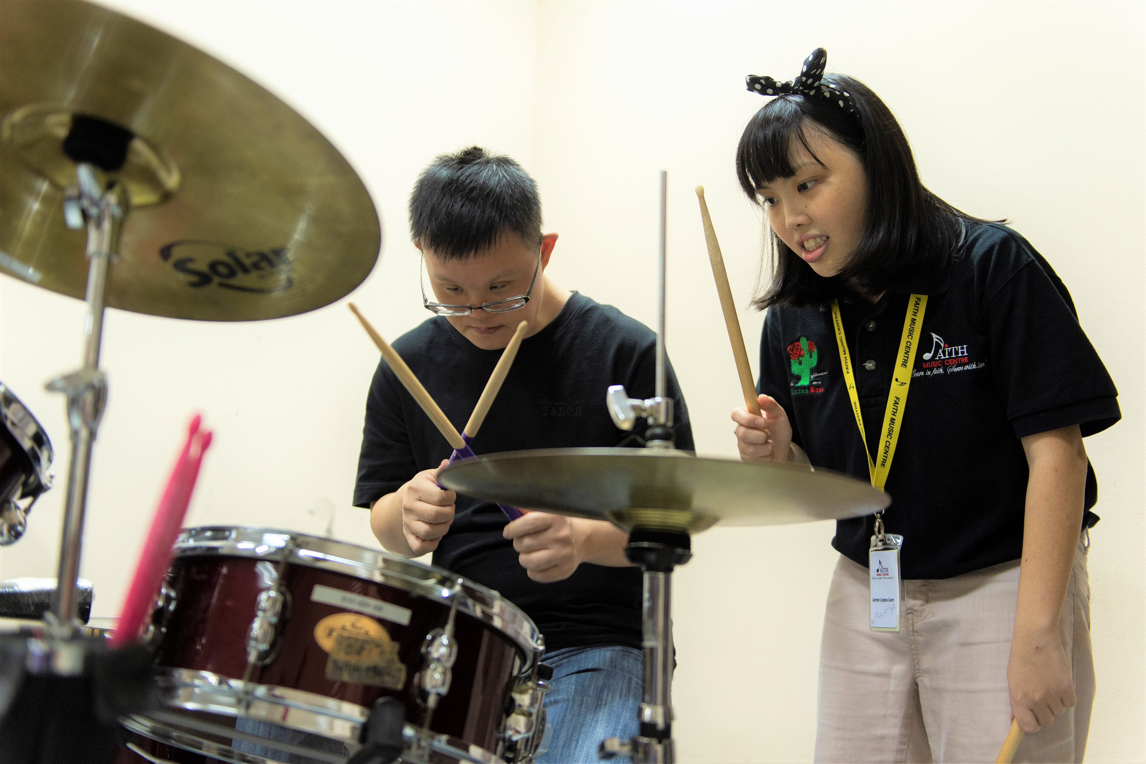 Two youth with special needs playing the drums at Faith Music Centre