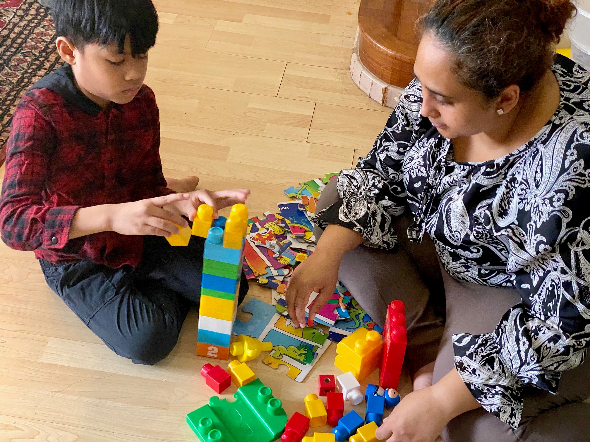 Farah playing with her son, Ilhan, using giant building blocks. Ilhan was diagnosed with ASD at age 4.