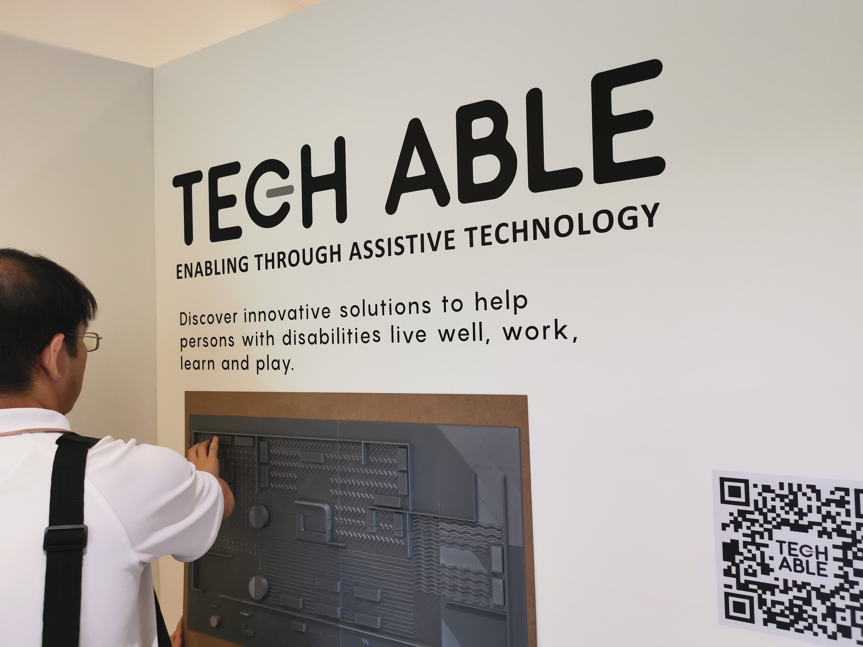 Visitor using the tactile map which features Braille and three-dimensional structures at one of the entrances of Tech Able.