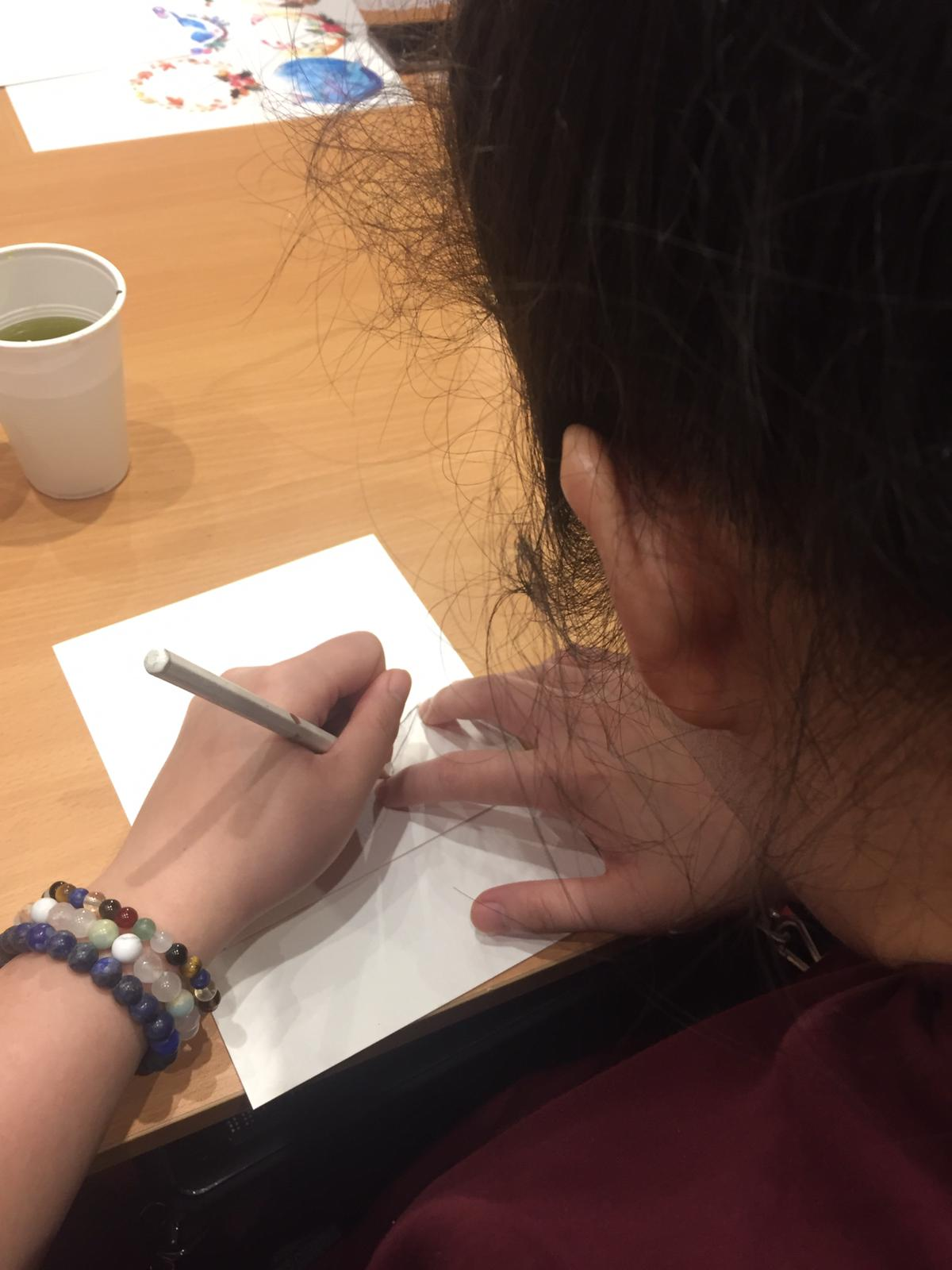 Siew Ling tracing the shape of a bird on a card.