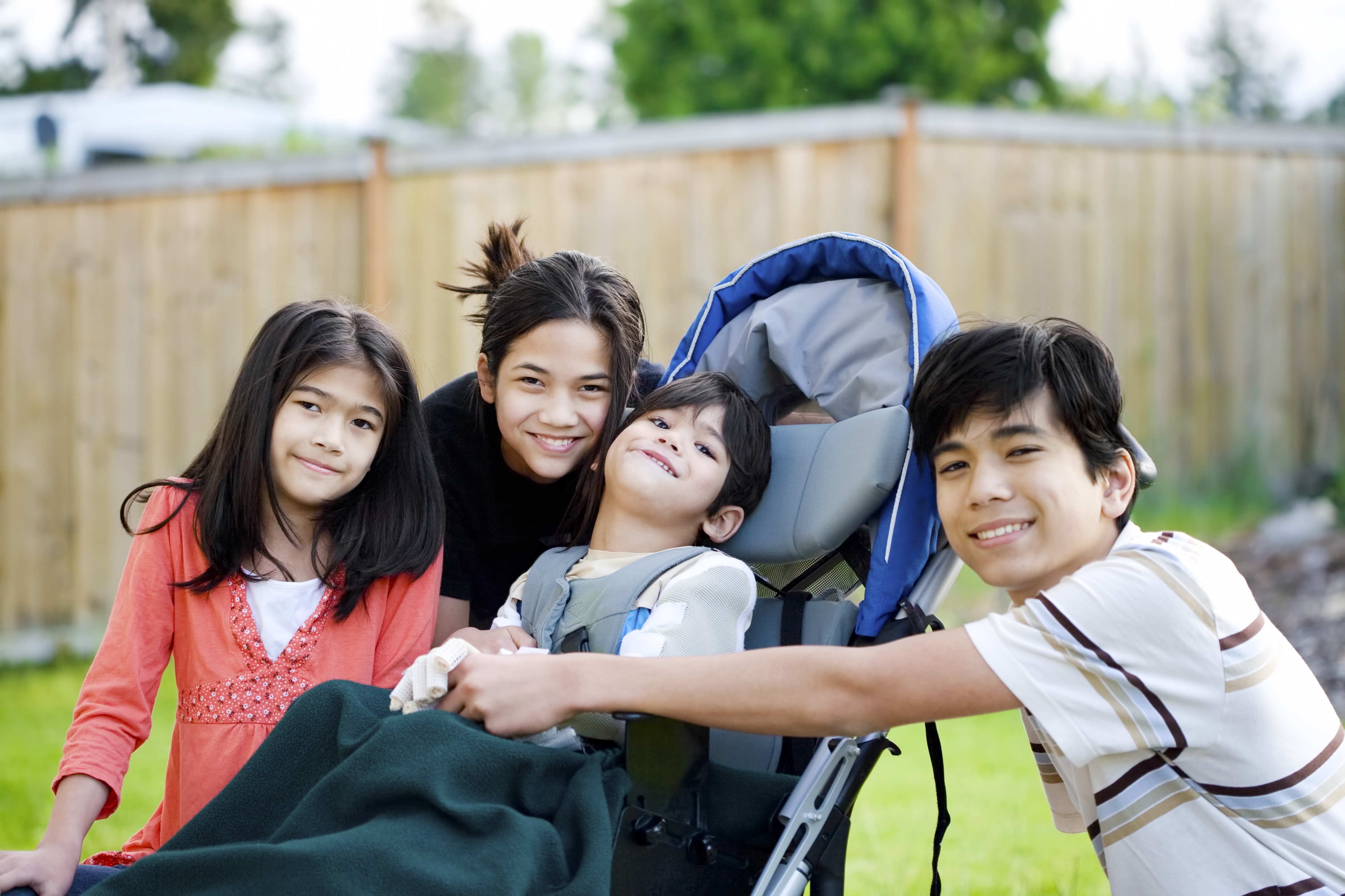 A stock photo showing a group of young caregivers with a young boy with disabilities in a pram.