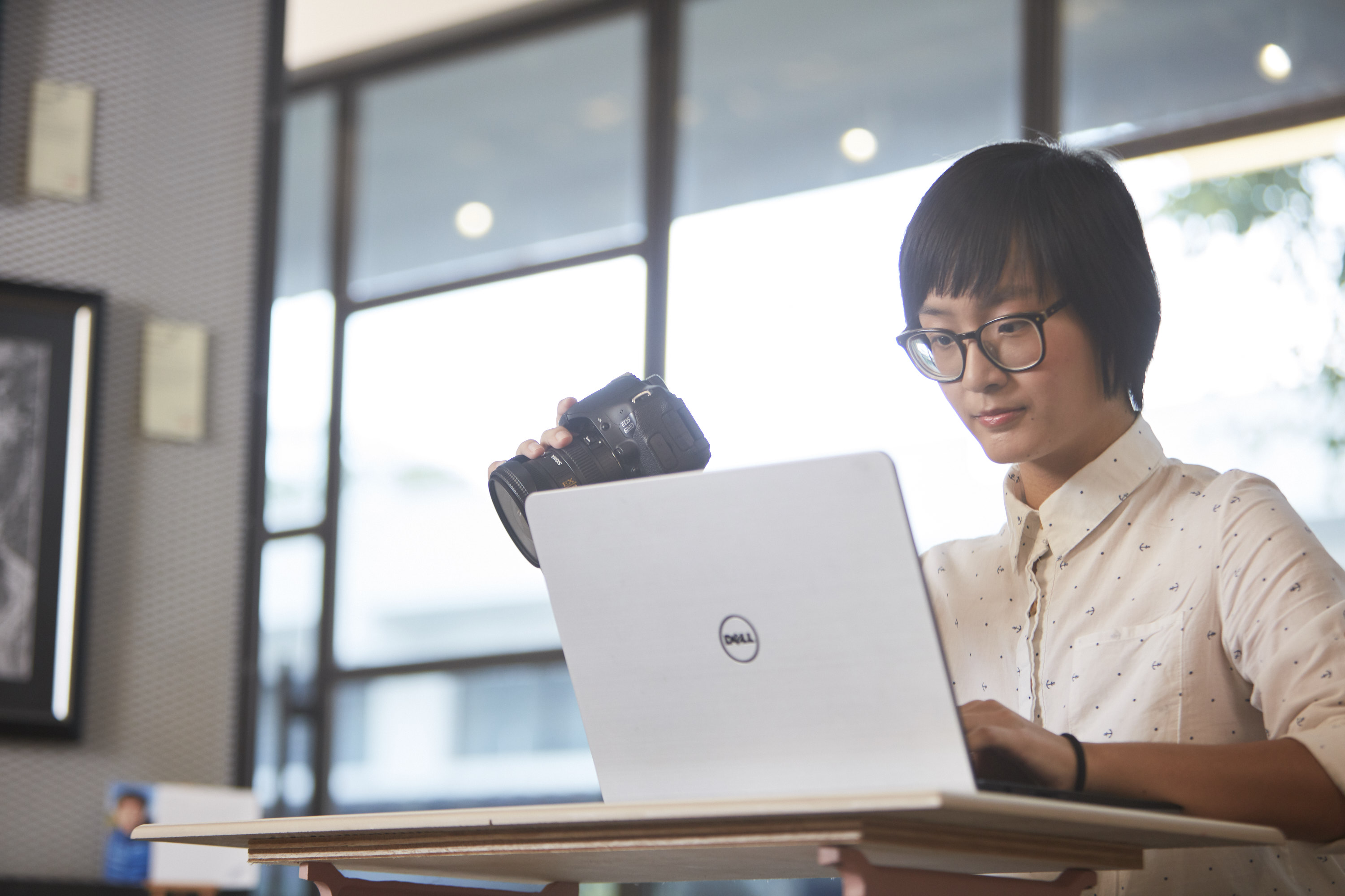 Image of a girl holding on to her camera while using her laptop