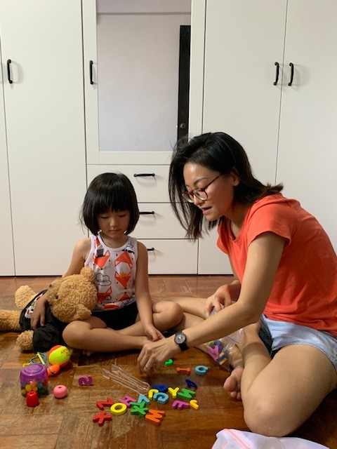 Wen Jing spending time with her daughter at home, playing with some alphabet blocks.