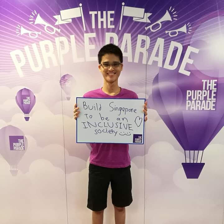 "The photo shows Wesley in a purple t-shirt holding up a sign that says ""Build Singapore to be an INCLUSIVE society  "" in front of a backdrop with ""The Purple Parade"" written several times on it."