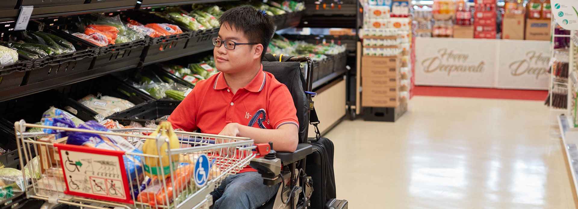 Young man in motorized wheelchair shopping for groceries in the supermarket